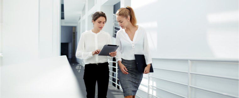 Two business women walking and talking
