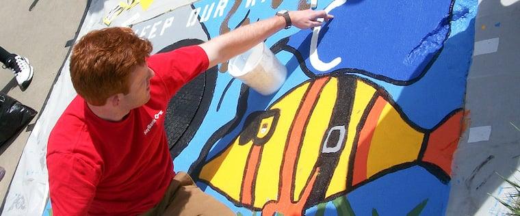 Key employee painting mural on waterway